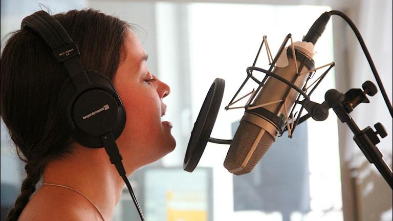 Miriam Karlsson står framför en mikrofon i radiostudion och sjunger. Foto: Rebecka Gyllin/Sveriges Radio.