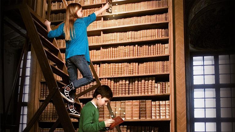 En flicka och en pojke klättrar på en stege i ett bibliotek och läser böcker.