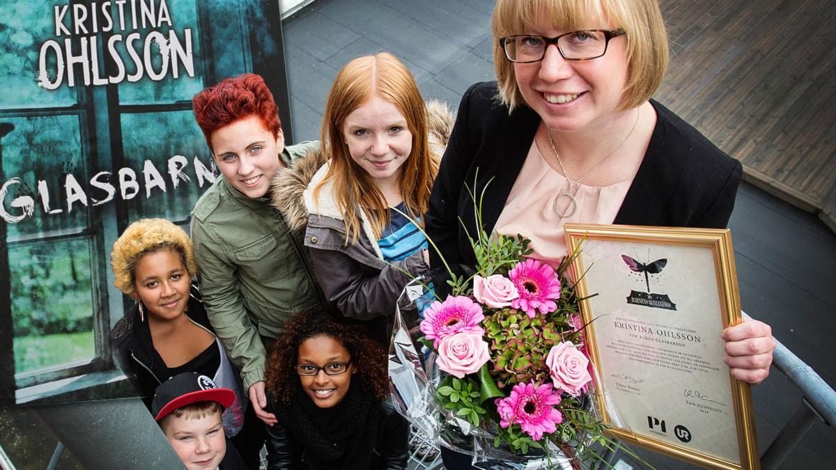Vinnaren av Barnens Romanpris 2013, Kristina Ohlsson, med juryn och boken Glasbarnen i bakgrunden. Foto: Martina Holmberg/Sveriges Radio