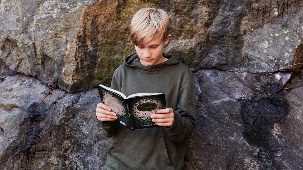 Morris Jones håller i boken Familjen av Cecilia Lidbeck.