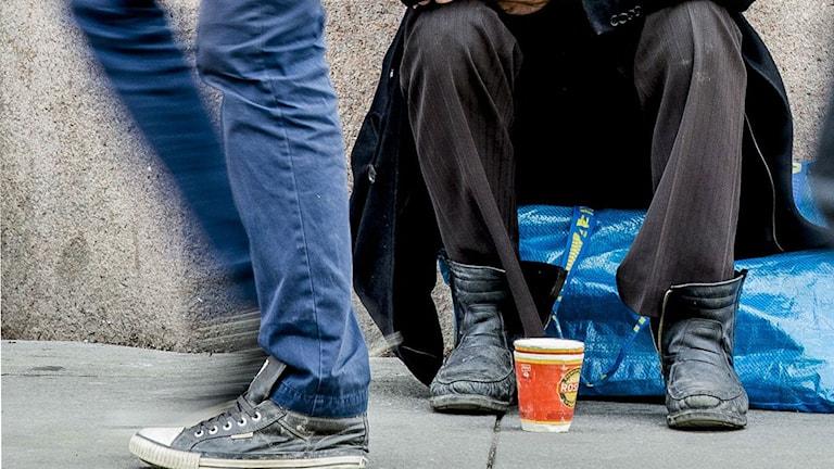 Fötter på en tiggare och förbipasserande. Foto: Stian Lysberg Solum/TT.