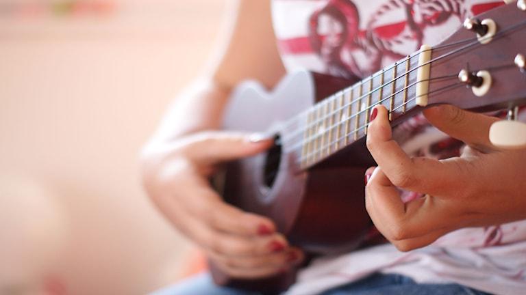 Kvinna spelar ukulele. Foto via Flickr