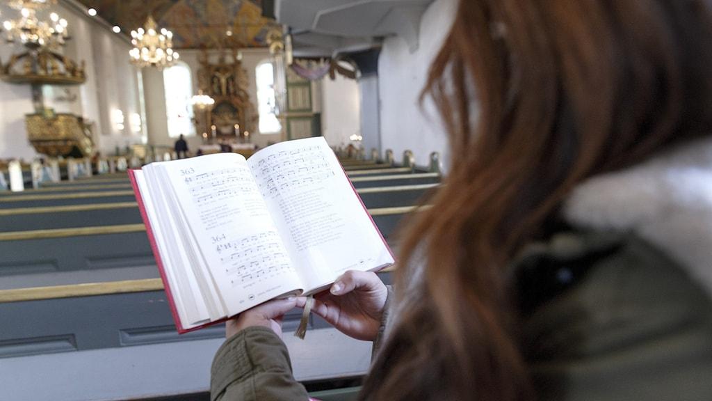 Bild: Kvinna med psalmbok i kyrka.
