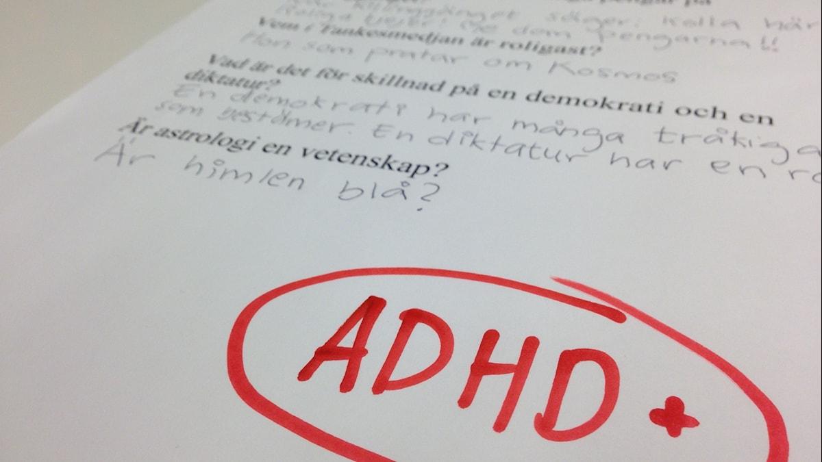 Ett prov med frågor och svar samt bokstäverna ADHD+ i stark röd färg. Foto: Jesper Cederstrand / Sveriges Radio