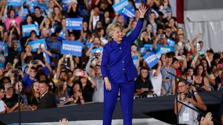 Hillary vinkar på en scen