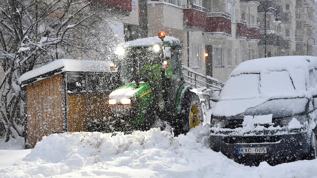 En snötäckt gata plogas av en traktor.