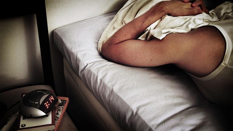 Bild på man som sover med kudde över huvuvdet.
