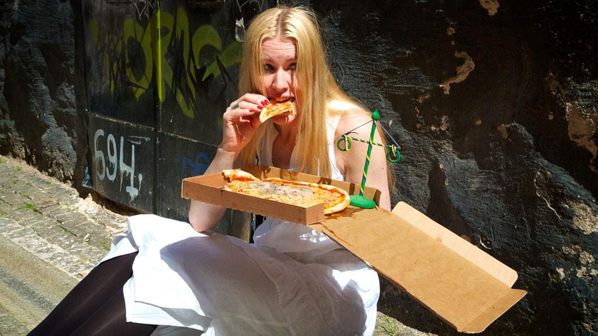 Kvinna äter pizza ur kartongen. Foto: Anders Elfström/Sveriges Radio
