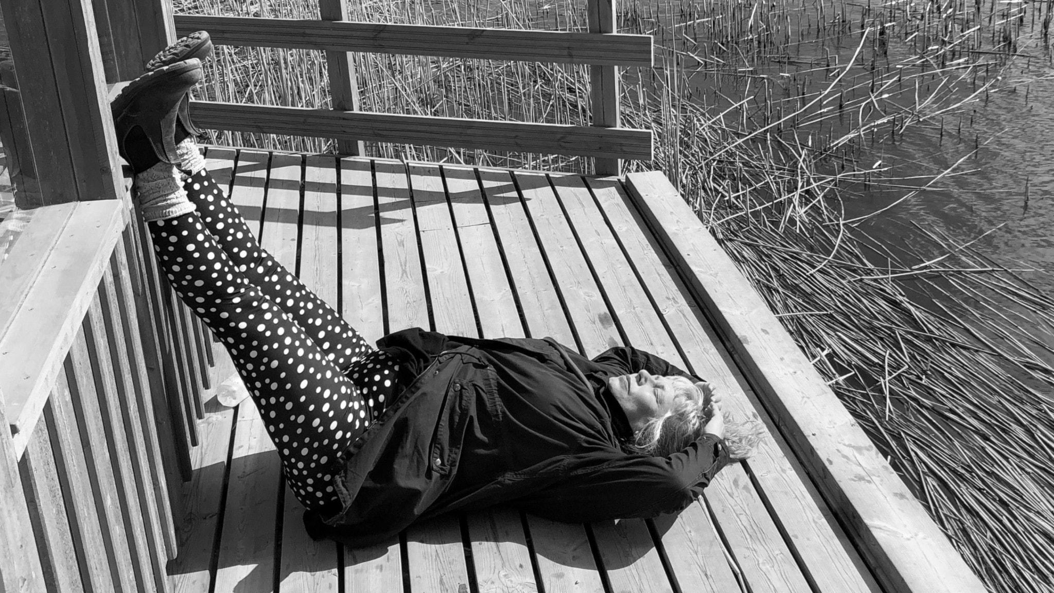 Stina ligger på en brygga med benen uppåt, lutade mot en trävägg. Bryggan omges av vatten och vass.