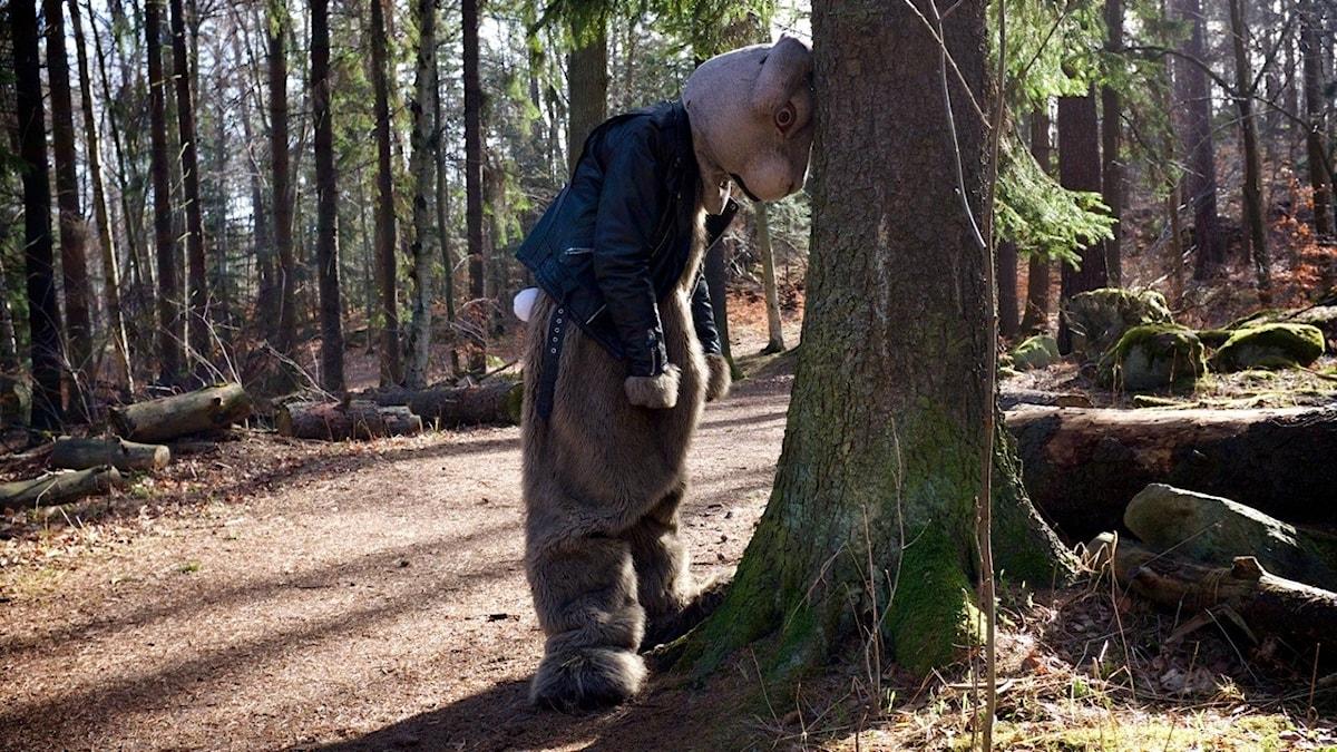 Person utklädd till påskhare står lutad mot ett träd.