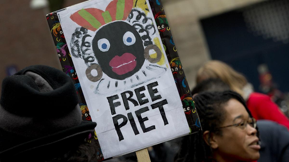 En kvinna demonsterar mot figuren Zwarte Piet i Amsterdam 2013. Foto: Peter Dejong / TT