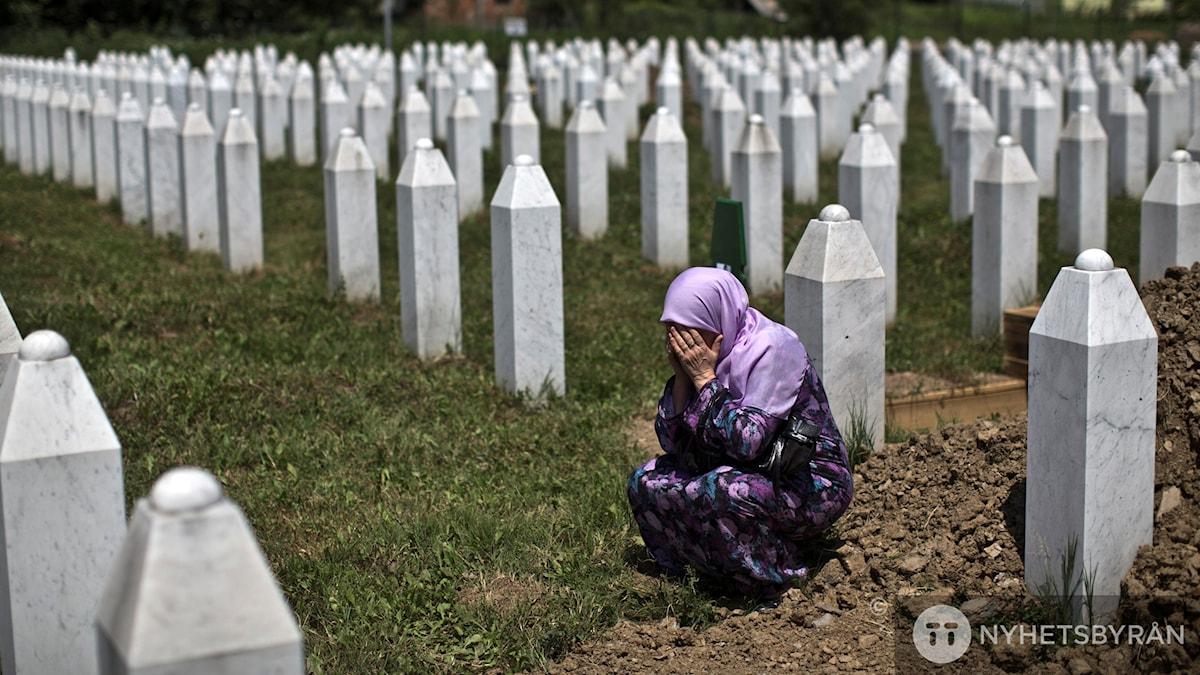 Kvinna ber vid sina släktingars grav, vid minnesplats för folkmordet i Srebrenica 1995. Foto: Marko Drobnjakovic/AP/TT