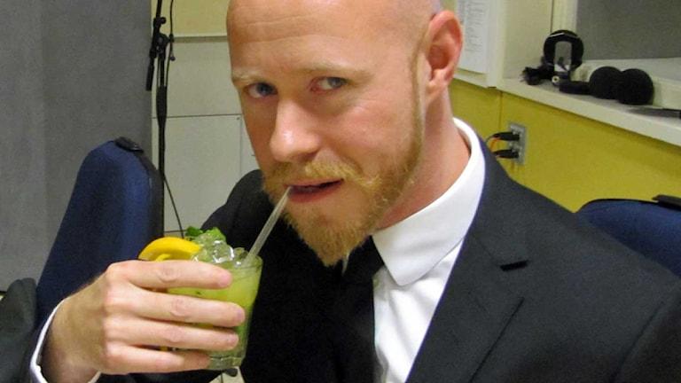 Anders Backlund - chef och gästproducent provsmakar fredagsdrinken eftersom Ibban är försvunnen i kulisserna. Foto: Ronnie Ritterland / Sveriges Radio
