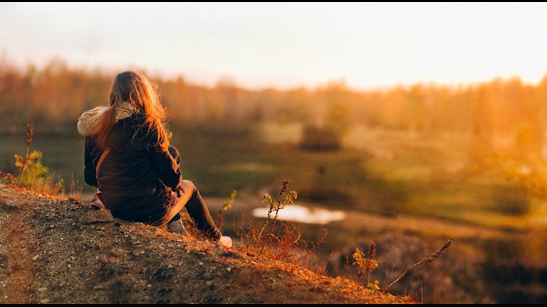 En kvinna sitter på en kulle och tittar ut över solnedgången.