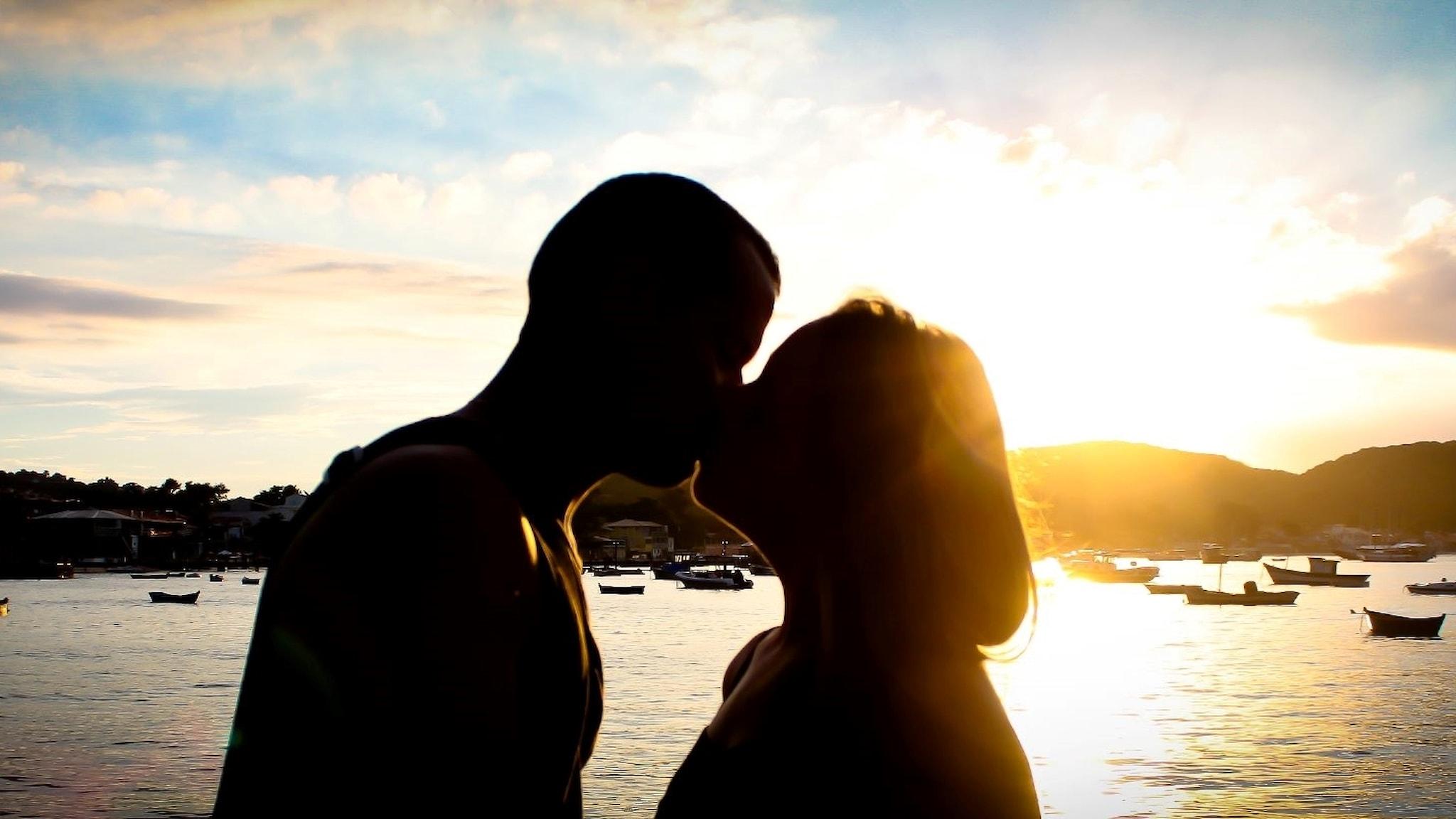 Ett par kysser varandra i motljus.