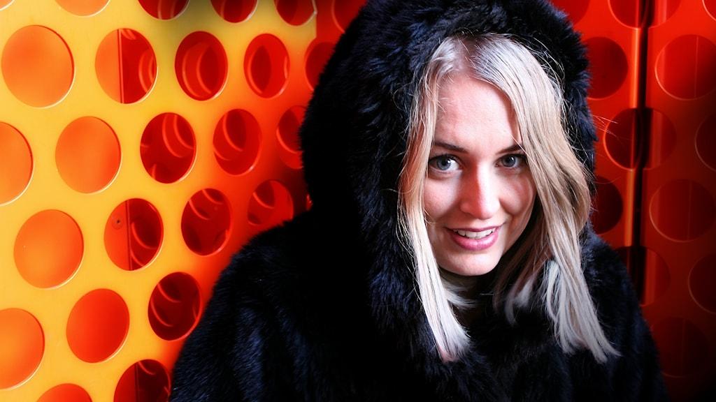 Bild på Mari som tittar fram ur en svart pälsluva. Hon står mot en orange bakgrund med en massa hål i.
