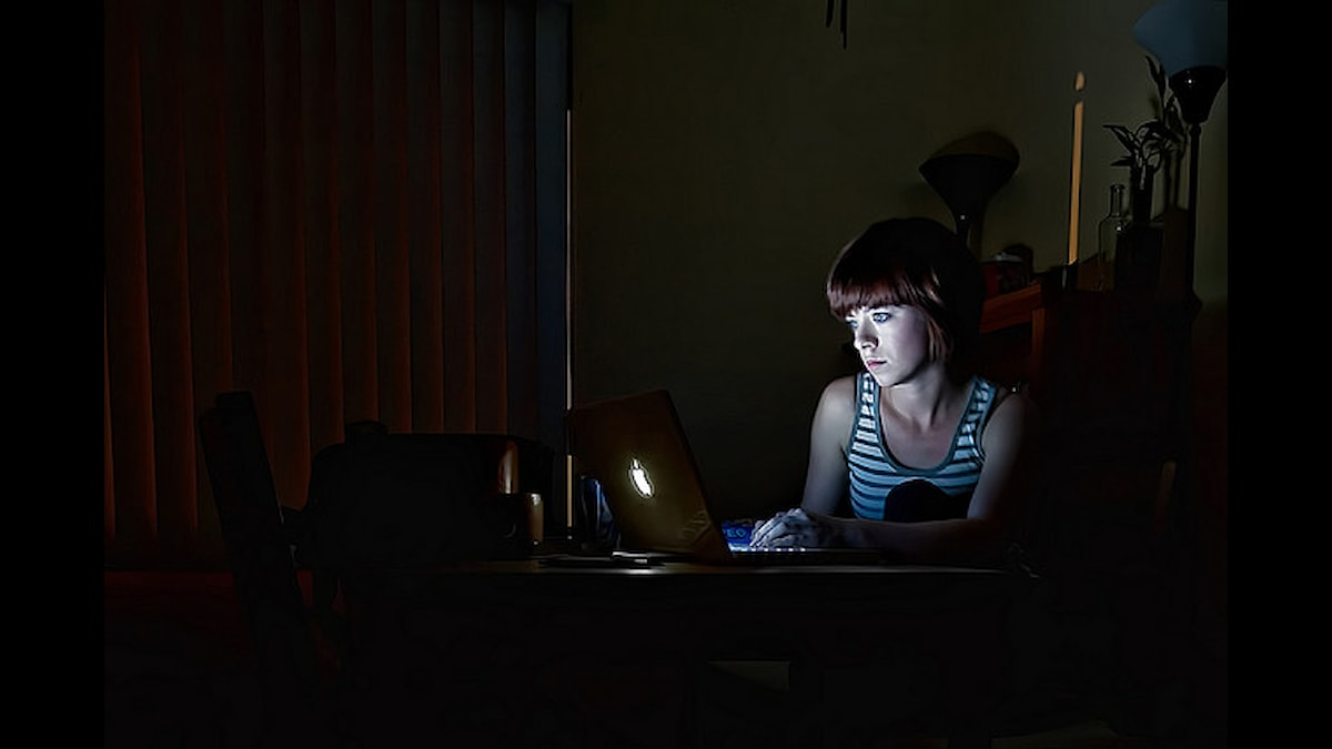 Tjej aitter vid en dator i ett mörkt rum. Foto: Corrie Howell/Flickr (CC BY-NC-ND 2.0)