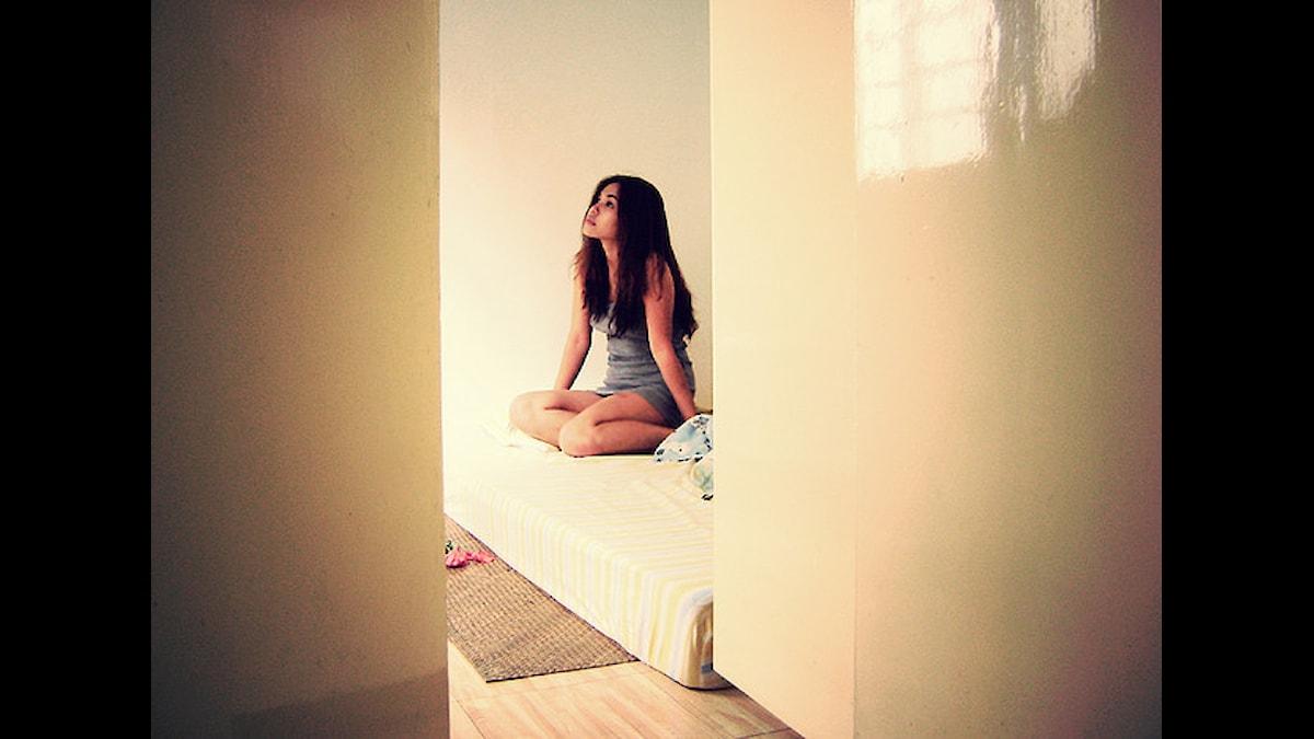 Tjej som sitter på sin säng.Foto: Helga Weber/Flickr (CC BY-ND 2.0)