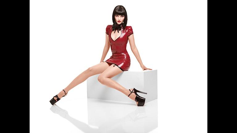 Kvinna med röd latexklänning.