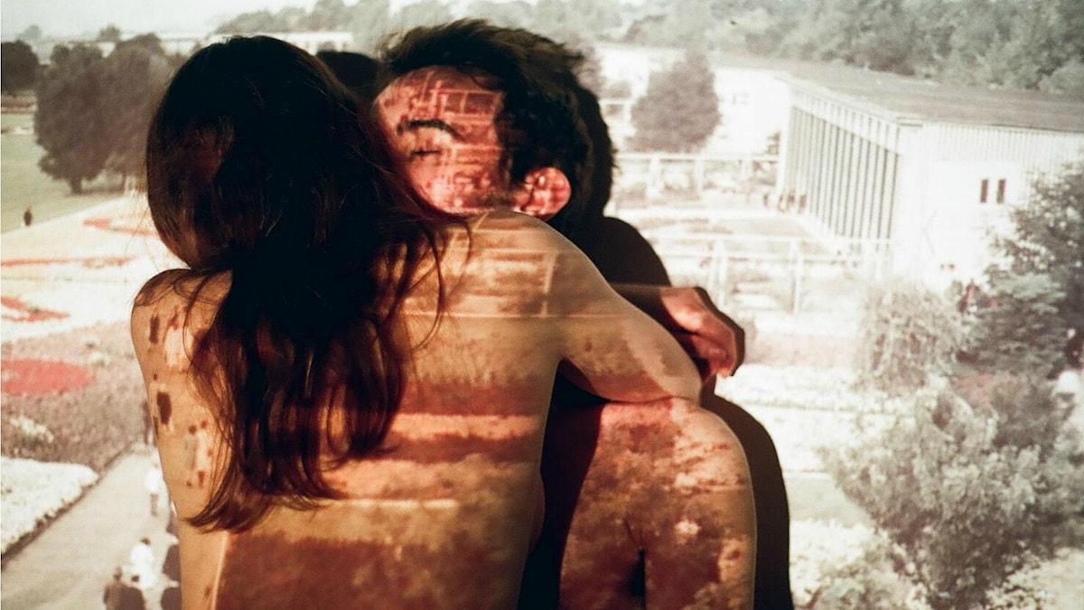 Par som kysser varandra i ljuset från en projektor.