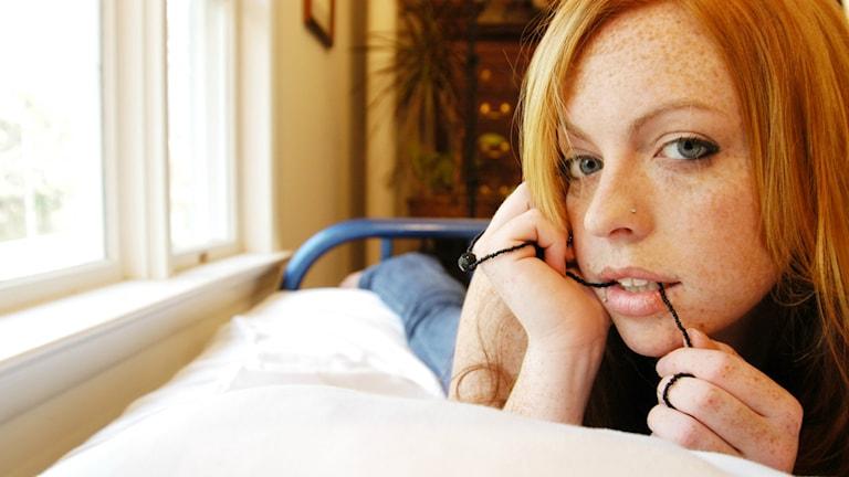 Närbild på en person som ligger i sängen och tittar in i kameran.