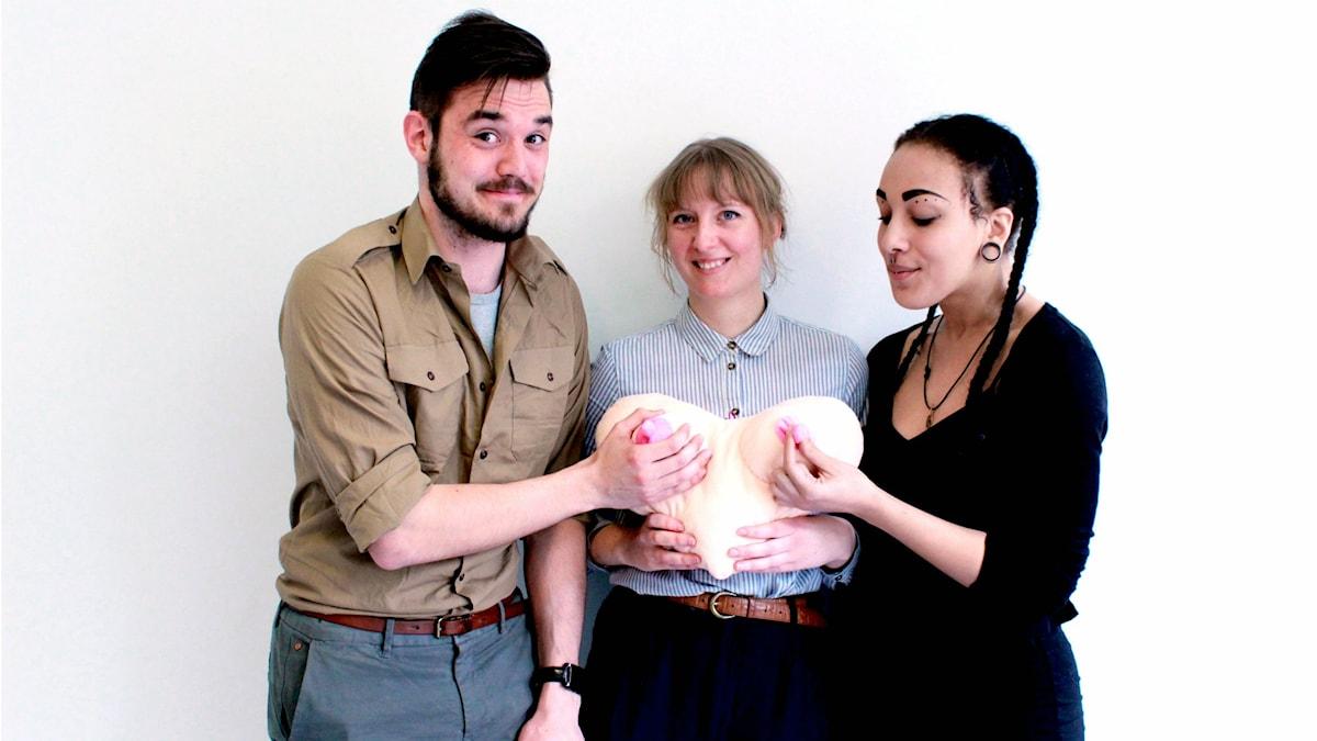 Panel som består av Niklas Sobieski, Olivia Whitehouse och Aïcha Coulibaly håller en kudde formad som två bröst.