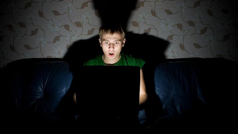 Person som tappar hakan framför en laptop.