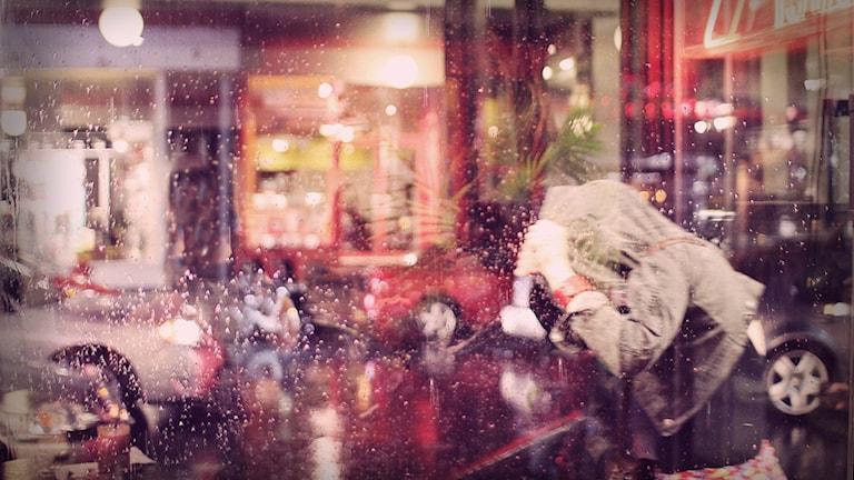 Person tar skydd från regnet under en jätteliten jacka.