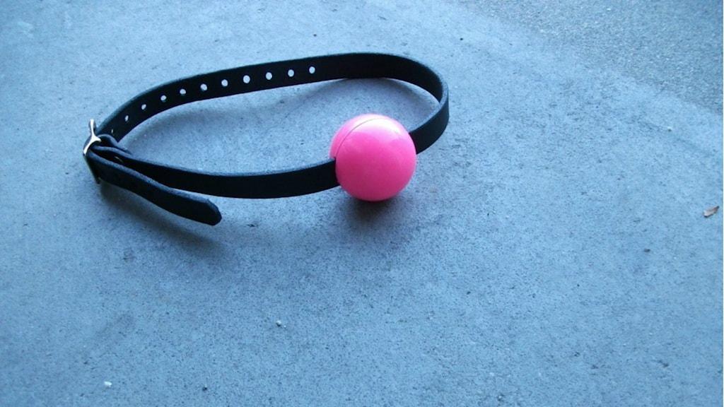 En rosa gag ball som ligger på marken
