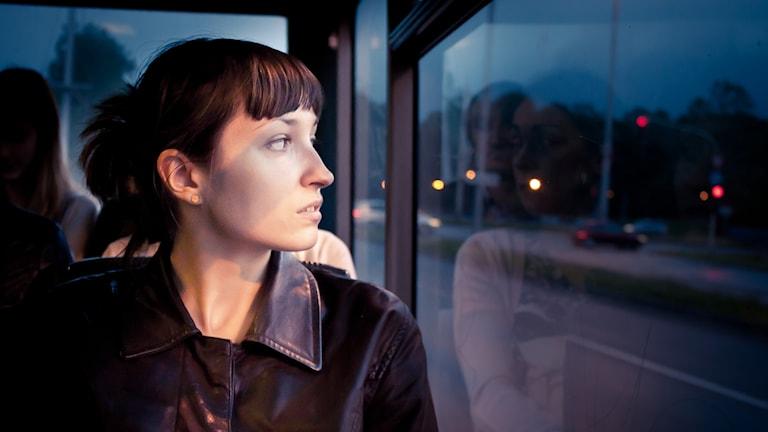 En kvinna som sitter och tittar ut genom fönstret.