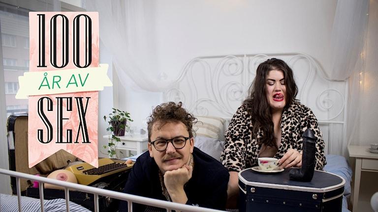 """Jimmie Lars ligger i en säng och ler. Maria Maunsbach sitter i sängen och har tungan ute. På vänster sida är det en stor rosa logga där det står """"100 år av sex""""."""