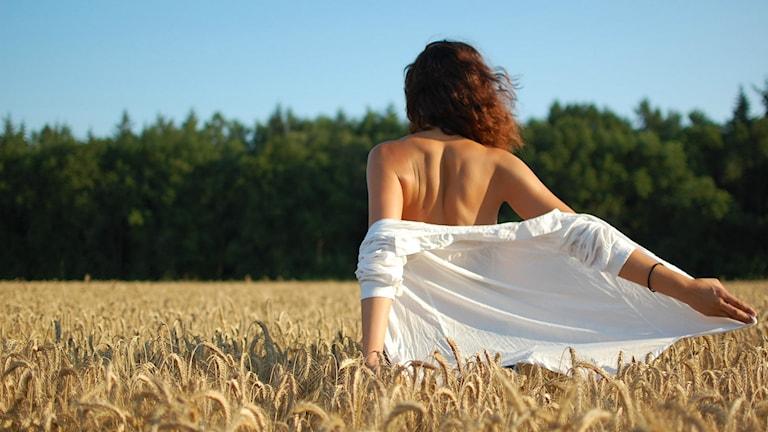 Kvinnligt kodad person går på ett fält.