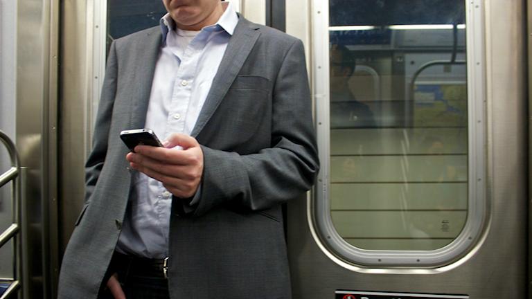 Man i kostym lutar sig mot tågvagnens dörrar.