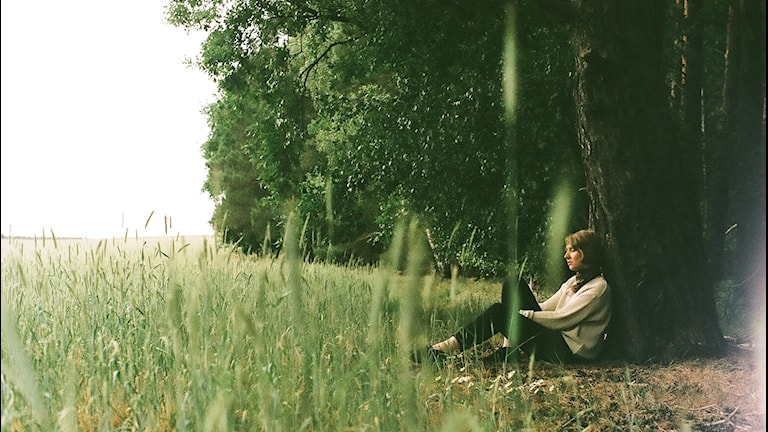 En kvinna sitter vid en åker och lutar sig mot ett träd.