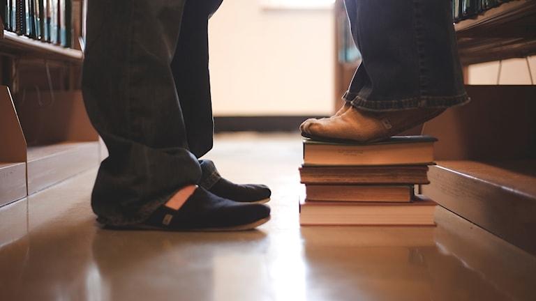 Två fötter som står i ett bibliotek.