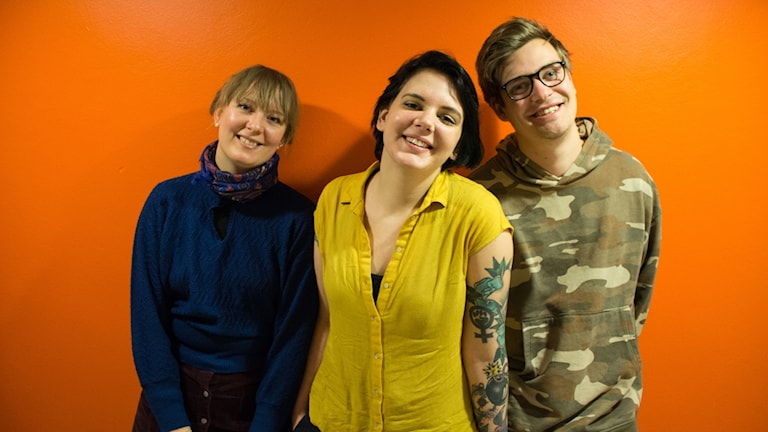 Panelen som består av Olivia, Vilska och Niklas står mot en orange vägg.