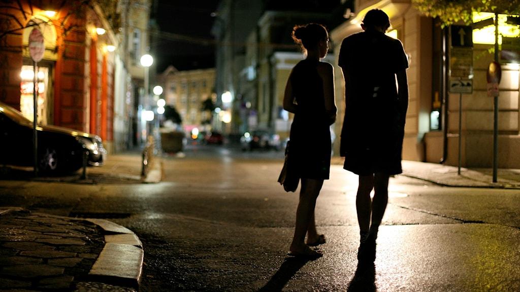 Två personer går i mitten av en gata. Det är mörkt ute, antagligen kväll eller natt.