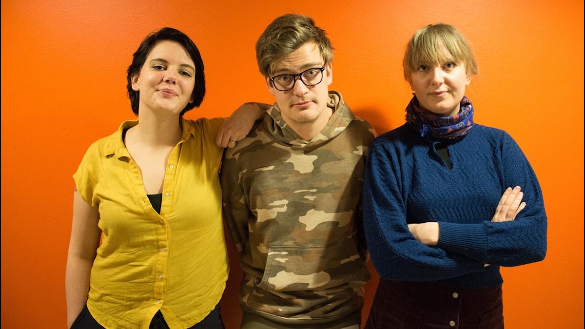 Panelen, Vilska Niklas och Olivia, står mot en orange vägg.