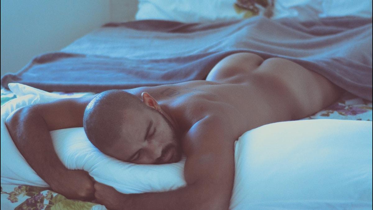 En man ligger på magen i en säng.