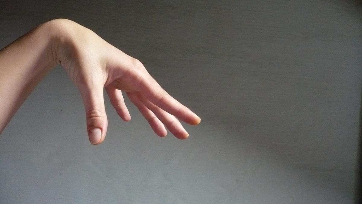 Hand som ser ut att gripa efter någonting.