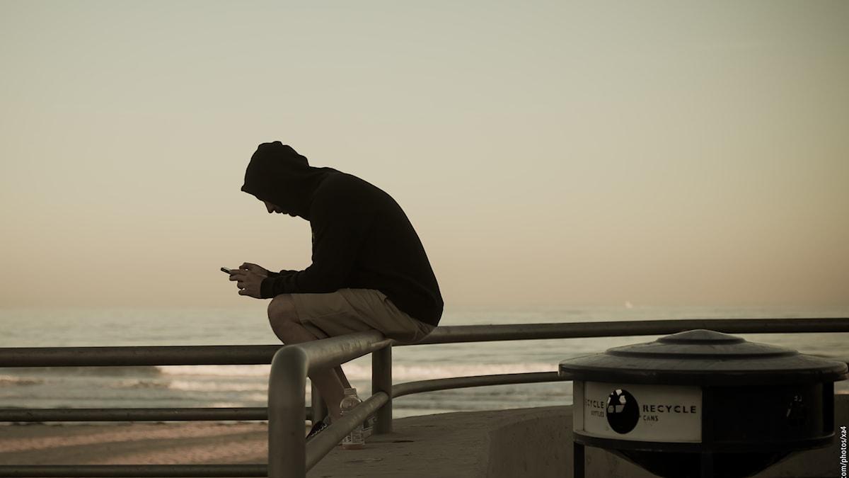 Man som textar vid havet.