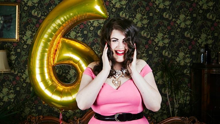 Maria Maunsbach ler. En stor heliumballong i form av en guldig sexa syns i bakgrunden.