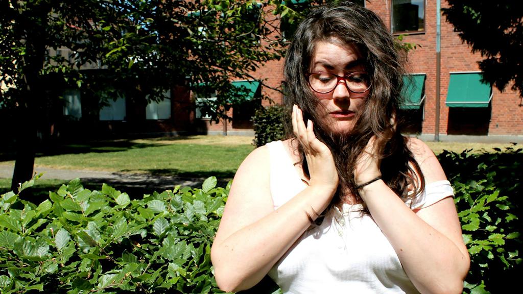 Maria står framför en buske. Hon tittar ner och ser ut att skämmas.