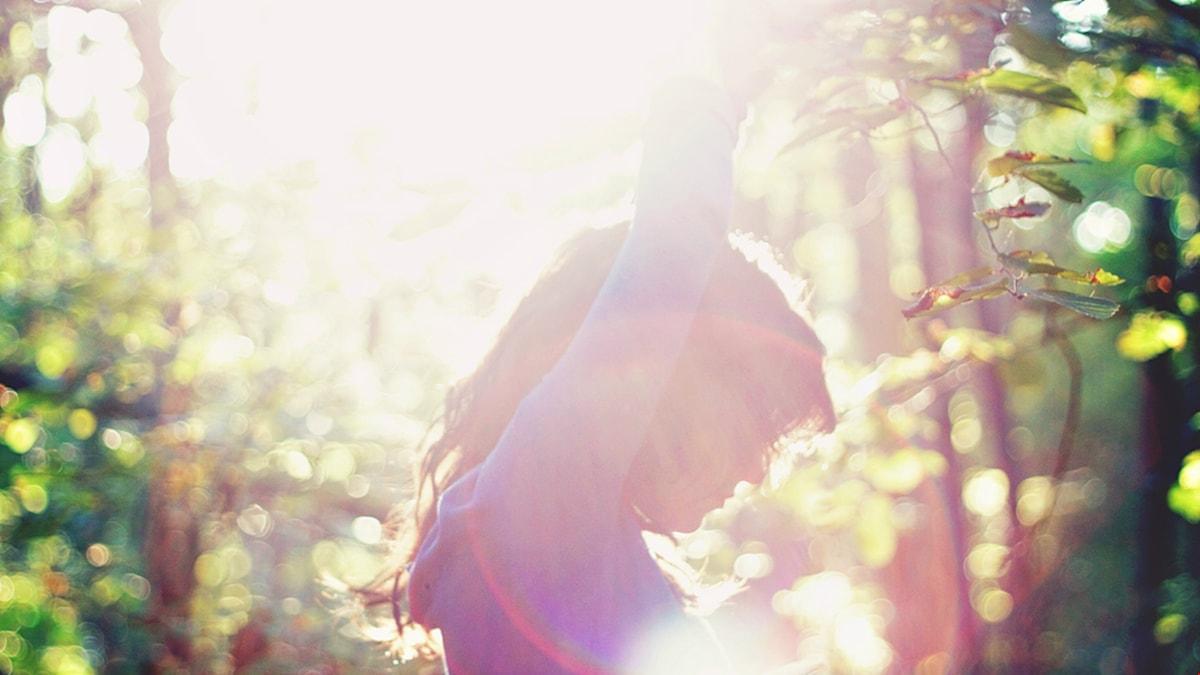 Person i skogsdunge. Solen skiner på personen.