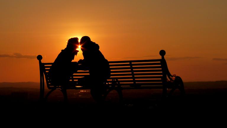 Par som vänslas i en idyllisk solnedgång.
