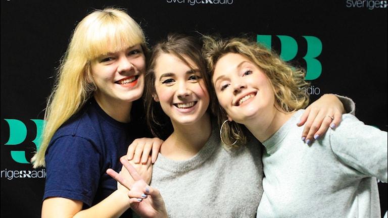 Filippa, Anna och Amanda står mot en svart vägg med P3-loggor på.