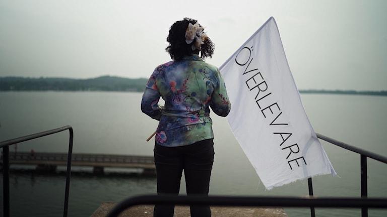 """En person står på en hög höjd och blickar ut över ett öppet vatten. I handen håller hon en vit flagga med ordet """"överlevare"""" på."""