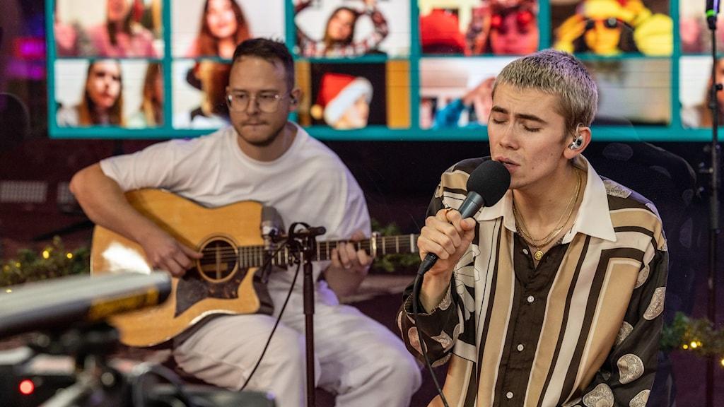 Felix sitter ner och sjunger. Han har en randig skjorta på sig. I bakgrunden syns en gitarrist och bakom dem en stor vägg med digital publik.