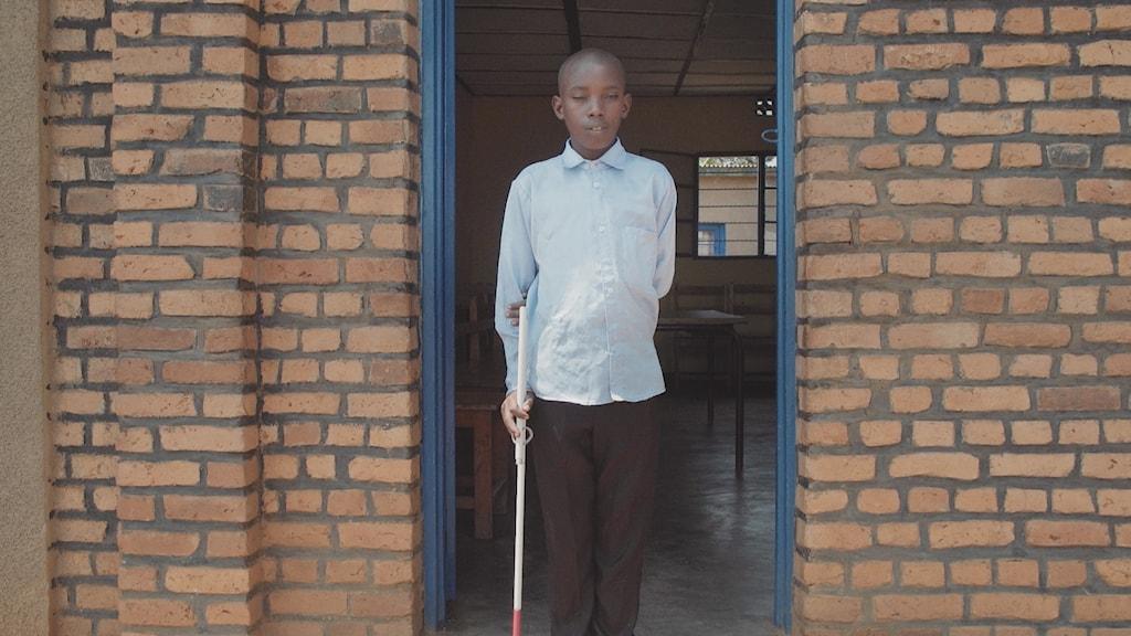 På fotot syns en pojke i ljusblå skjorta med vit käpp i en dörröppning.