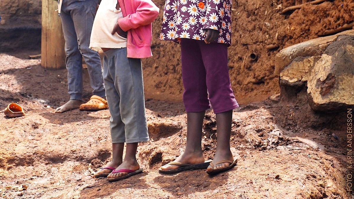 Två flickor står bredvid varandra på en sandkulle, bilden klipper av så att du inte ser deras ansikten.
